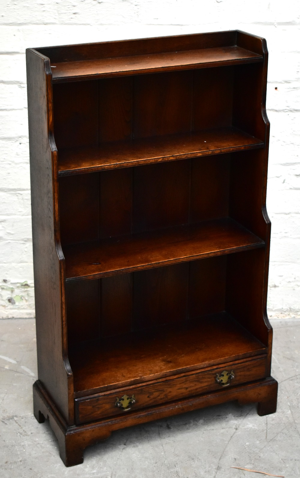 A reproduction oak waterfall bookcase with four open shelves above a base drawer, on bracket feet,