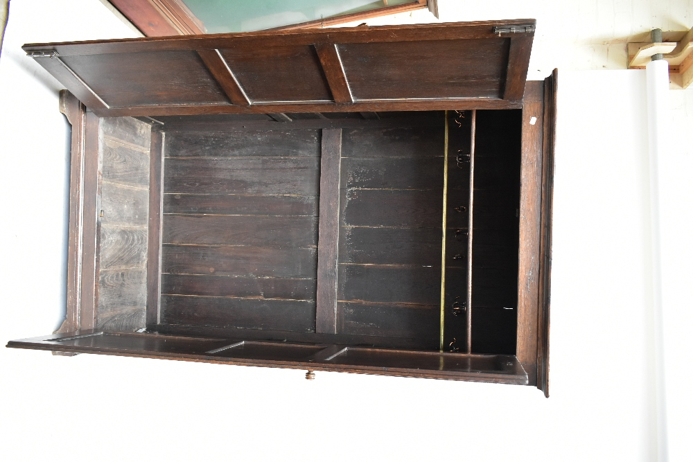An early 20th century oak wardrobe, the pair of linen fold carved doors enclosing rail, raised on - Image 4 of 4