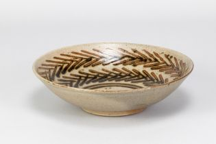 HELEN PINCOMBE (1908-2004); a shallow stoneware footed bowl with tenmoku breaking to kaki decoration