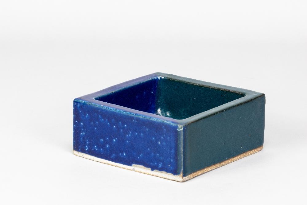 IAN AULD (1926-2000); a square dish covered in dark turquoise and indigo glaze, impressed IA mark,