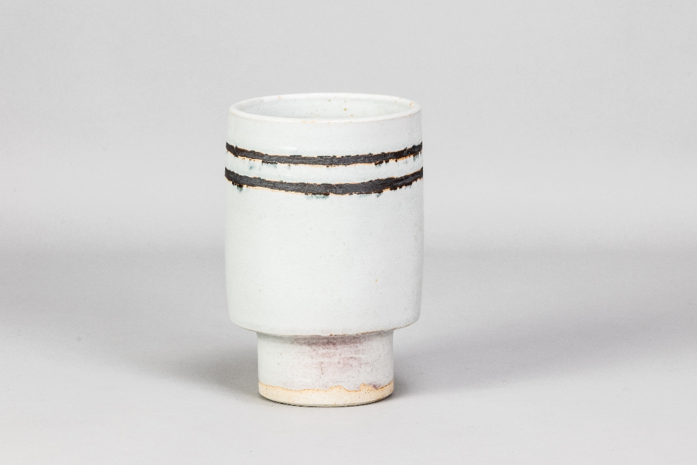 DEREK DAVIS (1926-2008); a cylindrical porcelain footed vase covered in chun glaze with manganese