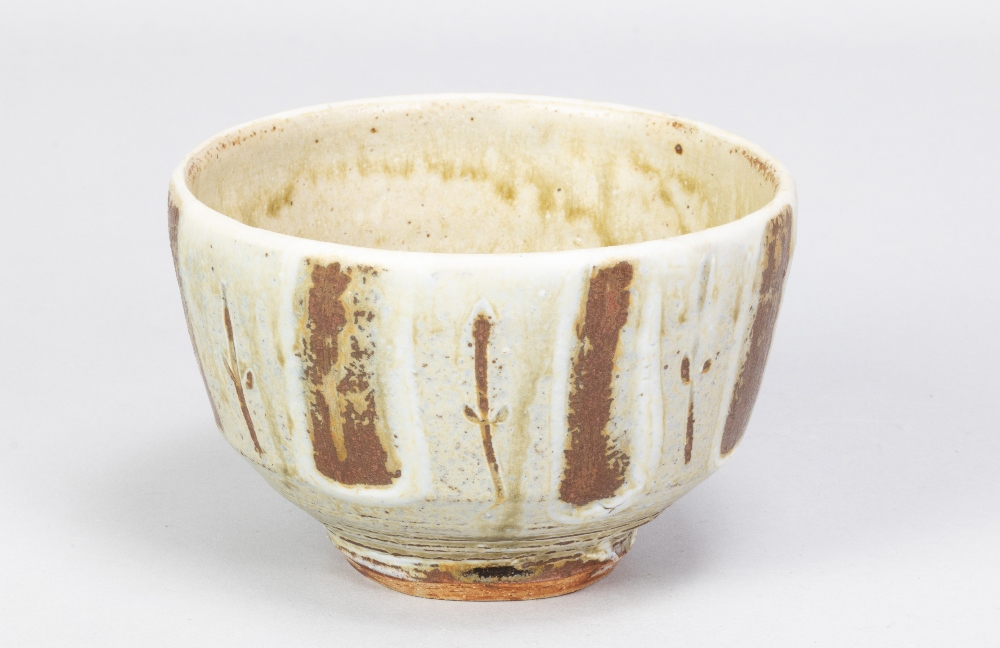 MIKE DODD (born 1943); a stoneware footed bowl covered in greeh ash glaze with wax resist and