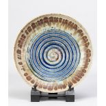 DEREK DAVIS (1926-2008); a shallow stoneware bowl with deeply incised spiral decoration covered in