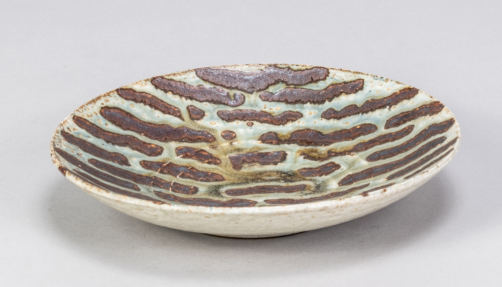 DEREK DAVIS (1926-2008); a porcelain dish covered in running green glaze on iron rich ground,