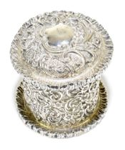 A late Victorian hallmarked silver cylindrical tea canister with allover embossed scroll decoration,
