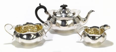 RF MOSLEY; a George V hallmarked silver three piece tea set of shaped oval form, with gilded