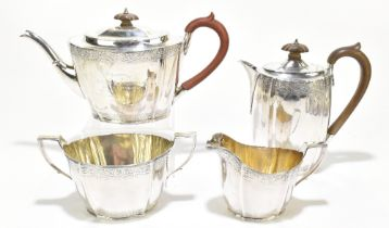 A George V hallmarked silver four piece tea set with band of engraved detail to both upper and lower