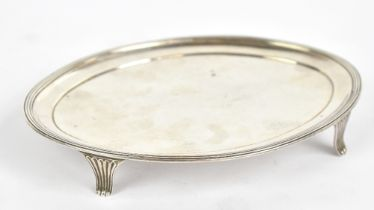 CRISPIN FULLER; a George III hallmarked silver oval teapot stand with reeded rim on four shaped