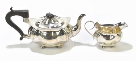 JOSEPH GLOSTER LTD; a George V hallmarked silver teapot and milk jug, each of shaped oval form