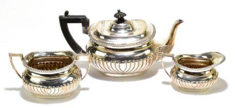 ARNOLD & LEWIS; an Edward VII hallmarked silver three piece tea set with gadrooned detail, London