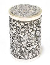A white metal cylindrical tea canister with pull-off lid and foliate detail to the body, stamped