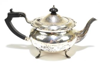 G BRYAN & CO; a George V hallmarked silver teapot of bulbous form with cast scrolling rim,