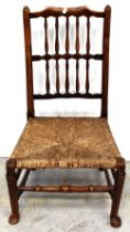 An 18th century rush seated nursing chair, the back rest with two rows of spindles,