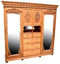 An Edwardian oak bedroom suite comprising triple wardrobe with dentil moulded cornice above central