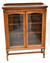 An early 20th century oak two-door display cabinet with simple frieze decoration above pair of