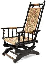 An American rocking chair upholstered in floral fabric.
