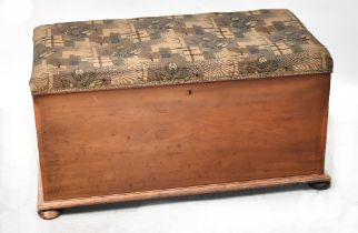 A mahogany ottoman with upholstered padded seat lid, raised on squat bun feet, 57 x 105 x 54cm.