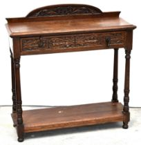 An early 20th century oak side table with single carved drawer,