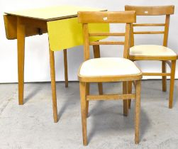 A 1960s yellow Formica covered drop-leaf kitchen table raised on rounded tapering supports and a