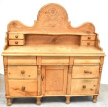 An early 20th century pine sideboard with arched back with carved decoration above a shelf flanked