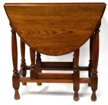 An early/mid-20th century oak gateleg table to turned baluster supports, length when extended 118cm.