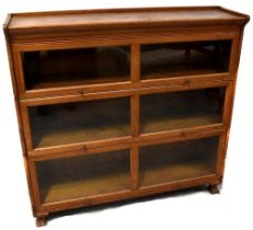 A Gunn oak three-section graduated stacking bookcase with glazed up-and-over doors,