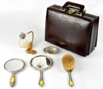 A hallmarked silver filled dressing table hand mirror with repoussé decoration of scrolls, shields,