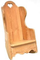 A rustic pine child's/doll's wing back rocking chair with heart-shaped motif to the back,