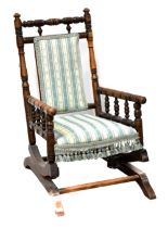 A late Victorian child's American rocking chair with turned supports and upholstered in a striped