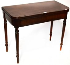 A George III mahogany fold-over table to tapering turned supports and peg feet,