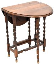 An early 20th century oak drop-leaf gateleg table with wrythen supports and stretchers,