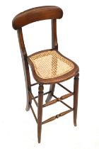 A Victorian child's correction chair with curved top rail, open back, lattice weave seat,