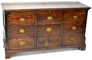An early 19th century oak mule chest, lift-up top above six faux doors,