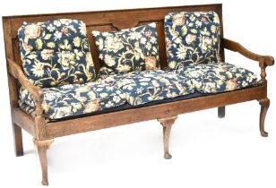 An early 19th century oak settle with four recessed carved panels to the back,