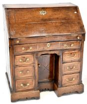 A George III oak bureau, drop-down desk top,