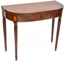 A 19th century mahogany fold-over tea table to tapering supports and peg feet,