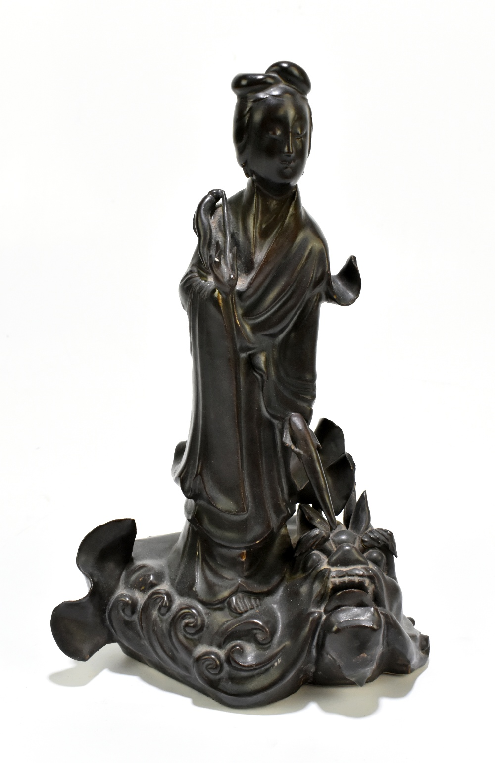 A 19th century Chinese porcelain figure representing Guan Ying standing on a mythical creature,