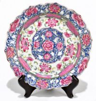 A late 18th century Chinese Famille Rose porcelain plate with scalloped edge, painted in enamels