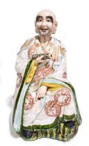 A late 19th century Chinese figure representing a seated scholar wearing a gown with relief and