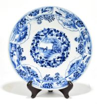 A late 19th century Kangxi style plate decorated in underglaze blue with floral panels, figures