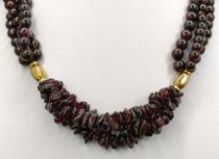 Garnet necklace, three strands, two gold plated elements in the middle, hook clasp, length 38cm