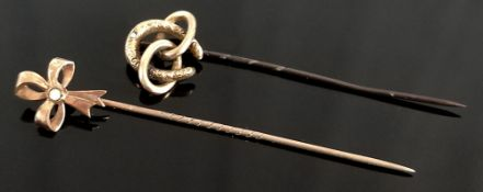 Two Art Nouveau lapel pins, one in the shape of a bow with full opal trim, length 6cm, the other