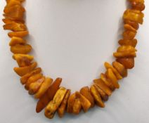 Long butterscotch amber necklace, natural amber stones increasing in size towards the center, length