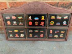 A Display Case Of 36 Car Badges