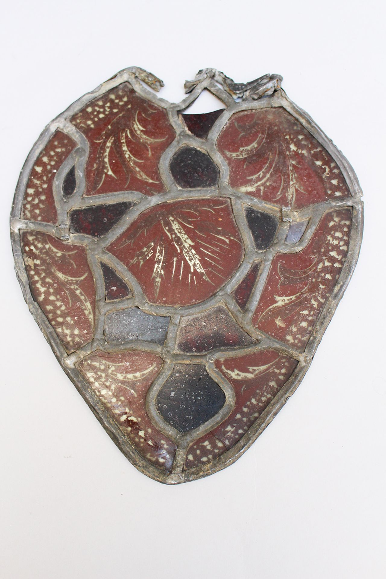 Glass window in medieval manner, red and black coloured leaves, in pewter frame,parts missing.