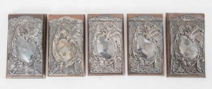 Lotto composto da cinque taccuini in legno e lamina argentata. Ciascuno di cm 19,8x11,3.