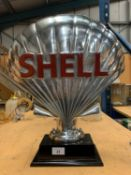 A LARGE CHROME SHELL LOGO SIGN ON A PLINTH HEIGHT APPROXIMATELY 50CM