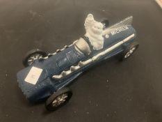 A VINTAGE CAST MICHELIN MAN IN BLUE RACING CAR