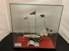 A WHITE METAL POSSIBLY SILVER MODEL OF A CHINESE JUNK IN A GLASS PRESENTATION CASE