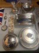 A LARGE ASSORTMENT OF SILVER PLATE ITEMS TO INCLUDE A HEATED MUFFIN DISH, LEMON SQUEEZERS, A